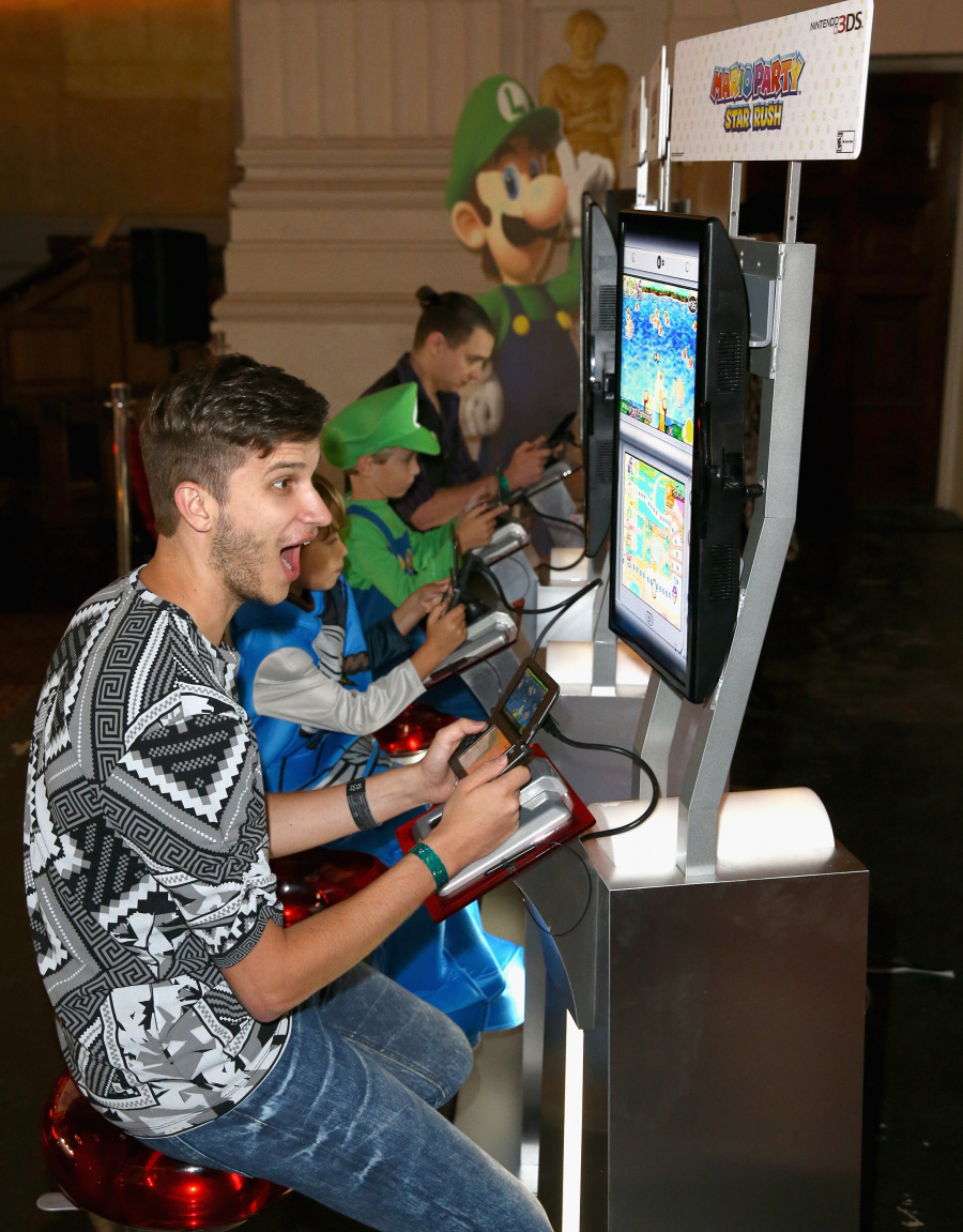 """In this photo provided by Nintendo of America, Zach D. of YouTube channel GhostRobo, plays a friendly round of competition in the Mario Party Star Rush game with guests at Starlight Children's Foundation's """"Dream Halloween"""" event on Oct. 22 in Los Angeles."""